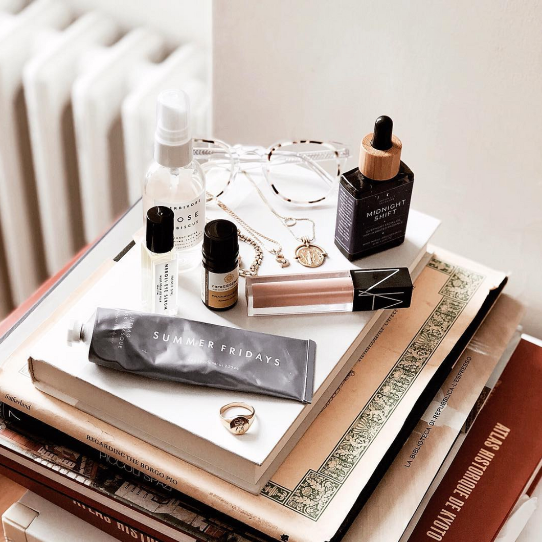 A bottle of Midnight Shift Overnight Facial Oil on top of a stack of book with other beauty products
