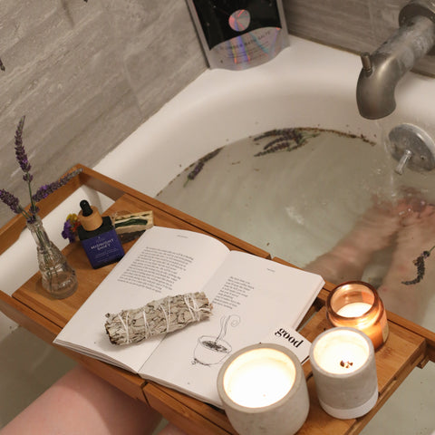 Bathtub with a tray holding a book, a few candles and some sage, with the legs of a woman visible in the water under the tray