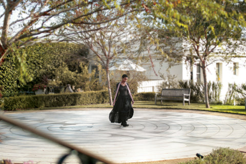 Woman in a black dress standing in the middle of the Peace Awareness Labyrinth & Gardens