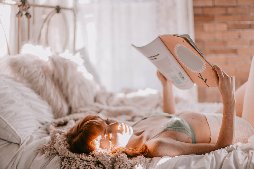 woman laying on bed while reading a magazine