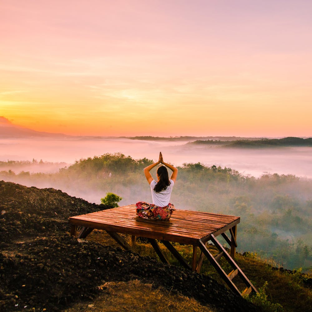 Woman meditating during sunrise in the mountains