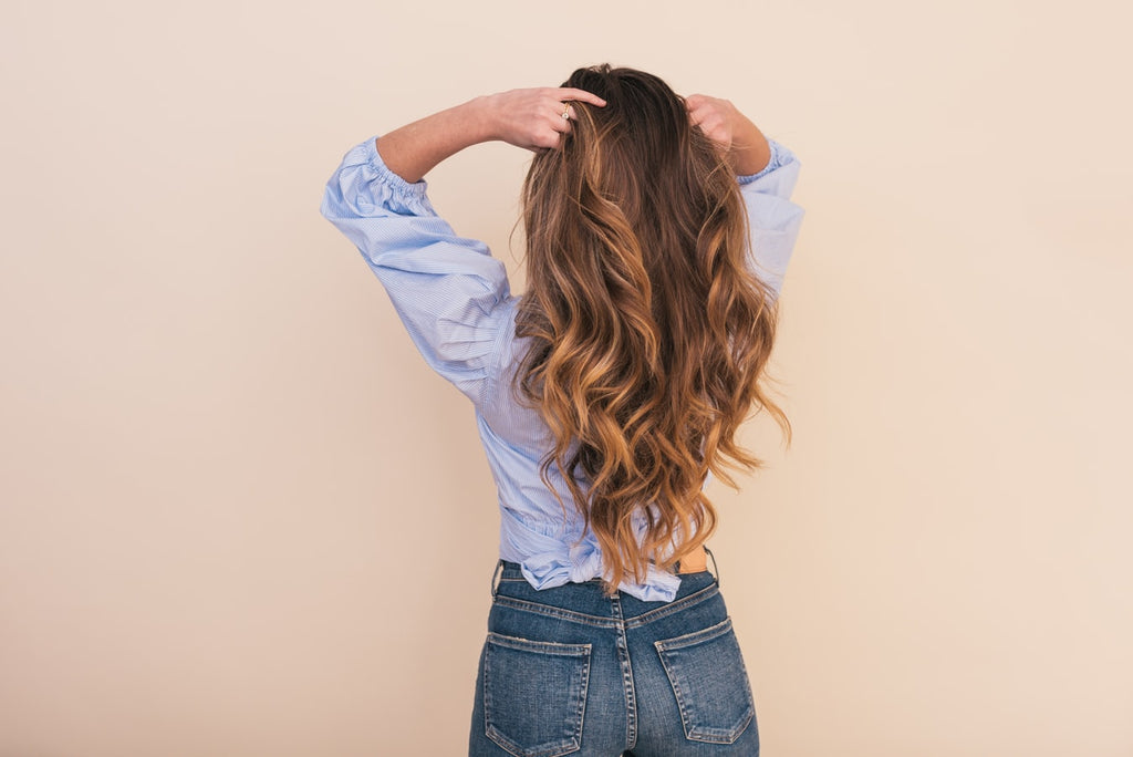 Girl facing wall with long hair showing her curls and heathy hair