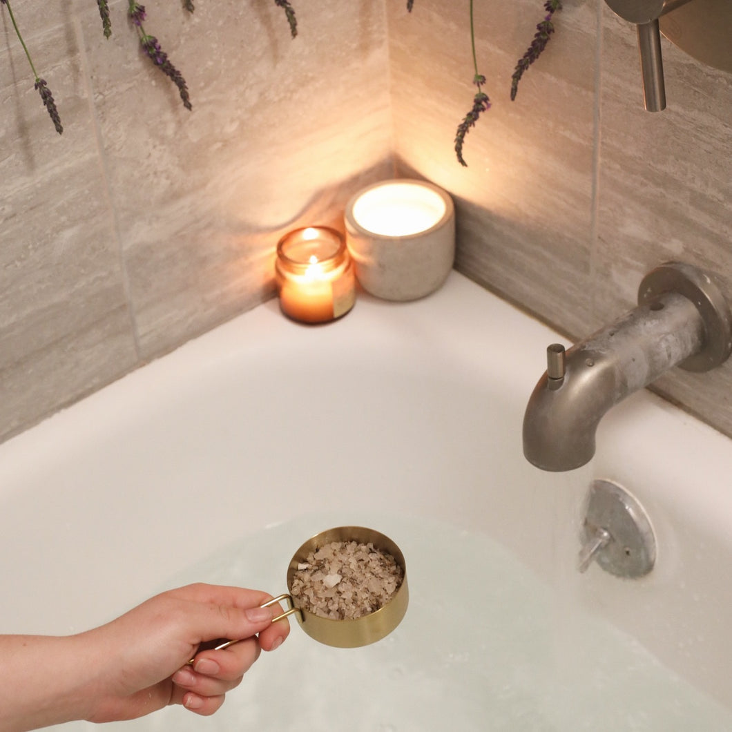 Hand pouring a cup of Slumber Bath Salts into a tub full of water, with two lit up candels on the side of the tub