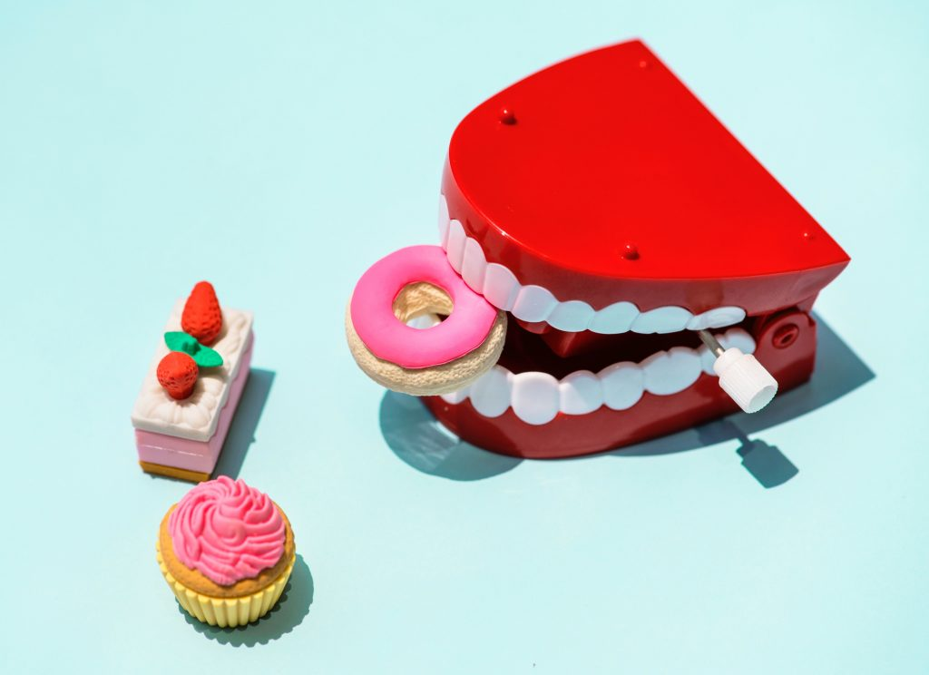 Plastic teeth holding plastic doughnut next to piece of cake and cupcake