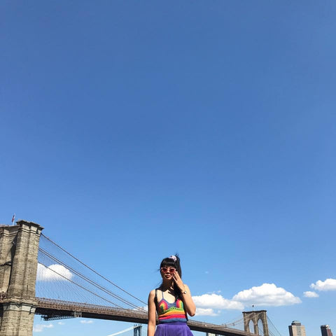 RC Shen in New York against blue skies and Brooklyn Bridge