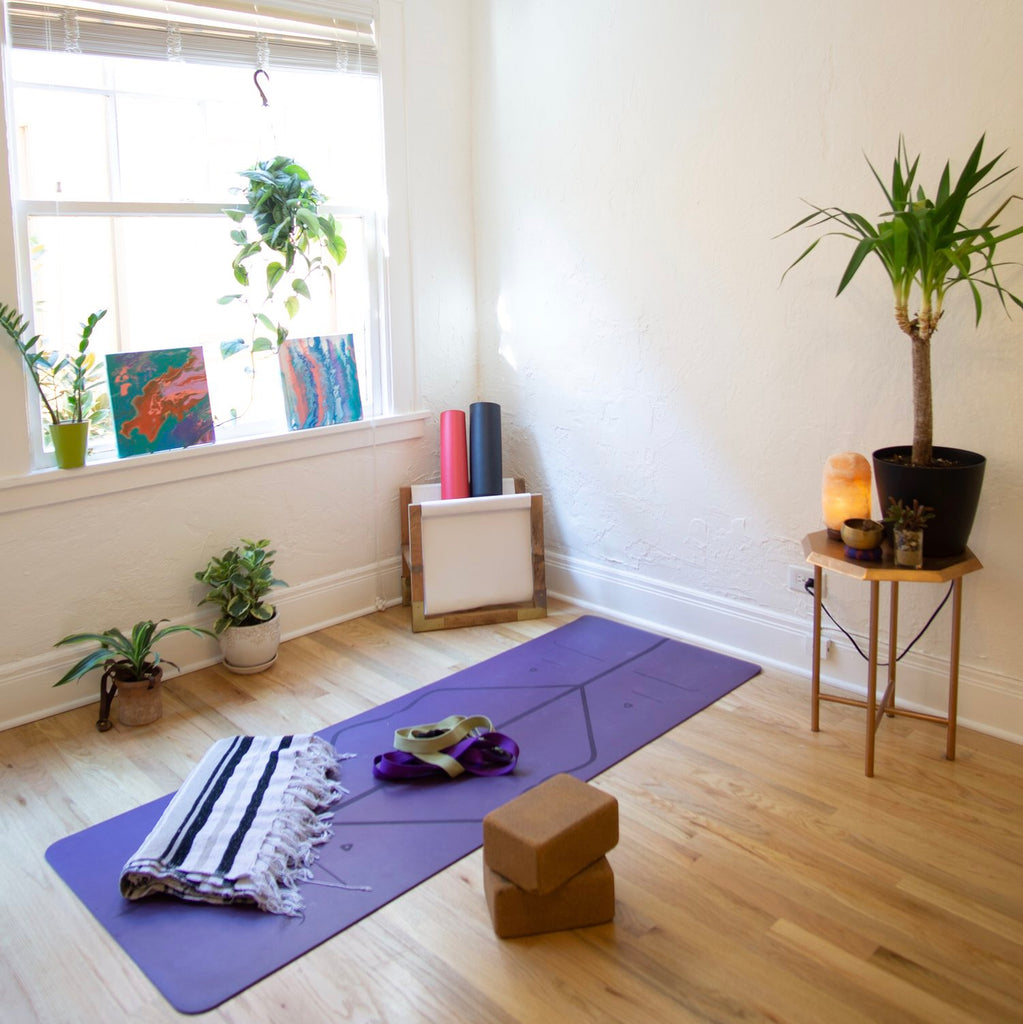 Room with personal home yoga set up that includes: purple yoga mat, brown yoga blocks, and blanket.