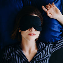 Girl lying on blue bed with soft silk black eyemask