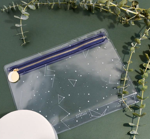 Transparent TSA-approved Constellation Travel Pouch with white constellation prints and a gold zipper with a moon pull.