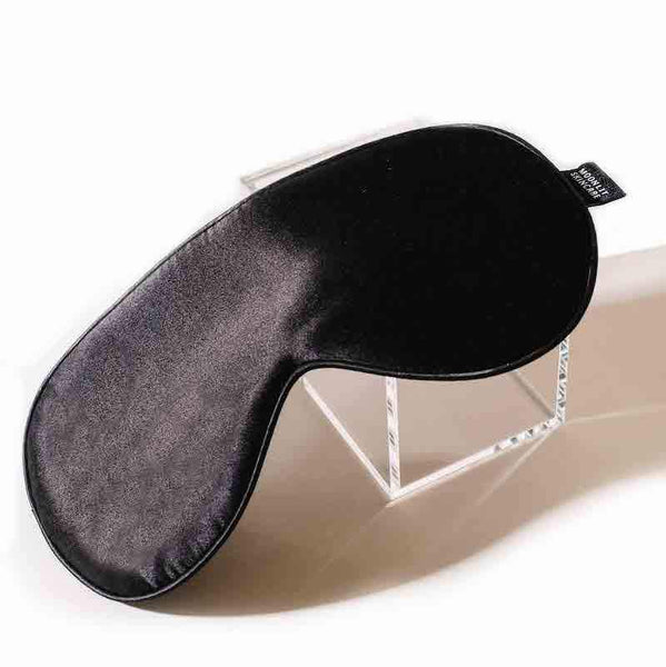 Black Sleeping Eye Mask with adjustable elastic strap on glass box
