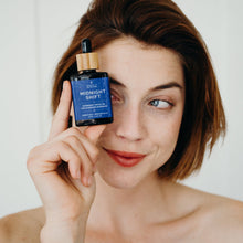Smiling girl holding Midnight Shift Overnight Facial Oil in front of left eye