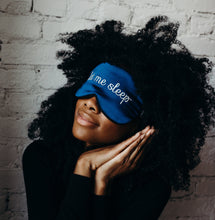 Girl with black curly hair in dark top wearing 'Let Me Sleep' Sleeping Silk Eye Mask, making sleep gesture with hands.