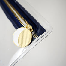 Close-up of moon zipper pull details - white crescent embedded within a gold circle.