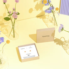 Product shot of Boma Jewerly's Waning Moon Studs in front of a yellow background and among pink and purplee flowers
