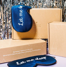 Silk 'Let Me Sleep' Eye Masks hanging on Moonlit Skincare boxes with New Years Eve backdrop