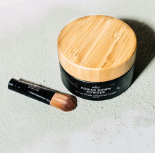 High angled shot of Powder Down Powder with bamboo lid detailing and included Powder Down Brush.