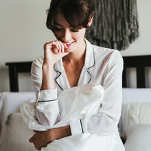 Girl in white silk pajamas smiling while holding a pillow fitted with Cloud 9 Silk Pillowcase in Ivory White.