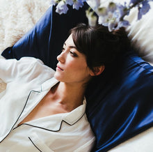 Girl in white silk pajamas, lying on pillow fitted with Cloud 9 Silk Pillowcase in Night-Sky Navy.