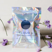 'Cloud 9' Night Sky Navy Blue Silk Pillowcase in iridescent packaging standing upright with purple flowers