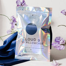'Cloud 9' Night Sky Navy Blue Silk Pillowcase in iridescent packaging standing upright in front of silk pillowcase draped in background