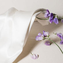 'Cloud 9' Ivory White Silk pillowcase lying against purple flowers