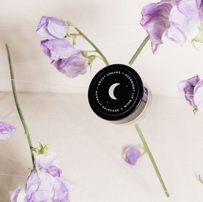 Angled view of Overnight Lip Balm with white crescent moon detailing on black lid