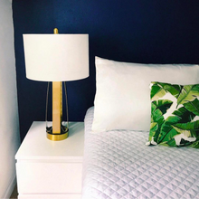 White Bedside with white and gold lamp, pillow fitted with Cloud 9 Silk Pillowcase in Ivory White, and leaf-patterned cushion.