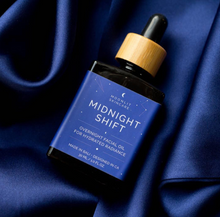Front view of Midnight Shift Overnight Facial Oil bottle with wooden detail and rubber dropper, against Navy Silk Pillowcase.