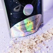 Slumber Bath Salts in packaging with salts scattered in front containing lavender, geranium, and frankincense essential oils to induce relaxing sleep