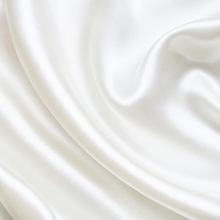 Close-up of smooth silk texture on ivory white pillowcase.