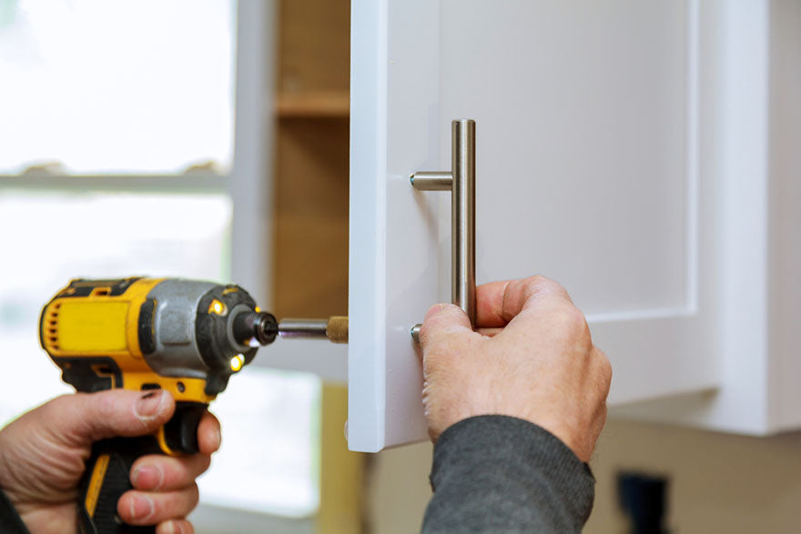 worker sets new handle on cabinet