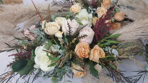 silver blue foliage and paler peach tones in the roses.