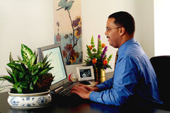 man at desk with plant and flowers