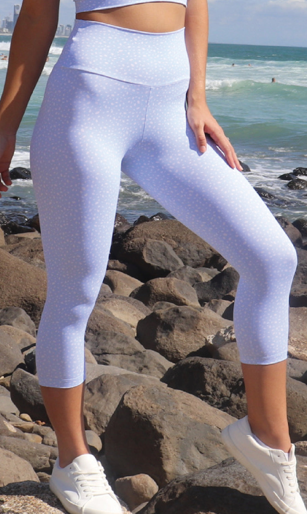 Girl on beach in white & blue cloud star dust print body luxe capri leggings