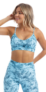 Front view of girl wearing blue tie dye blue crush print momentum bra with three horizontal back straps & matching ultra high waist leggings