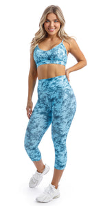 Front View: Girl with hand on hip wearing blue tie dye blue crush print ultra high waist capri leggings & matching racer back bra