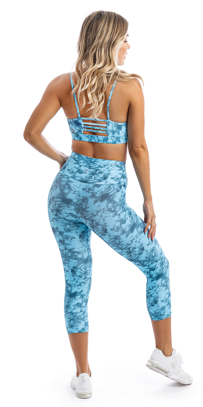 Rear View: Girl with hand on hip wearing blue tie dye blue crush print ultra high waist capri leggings & matching racer back bra