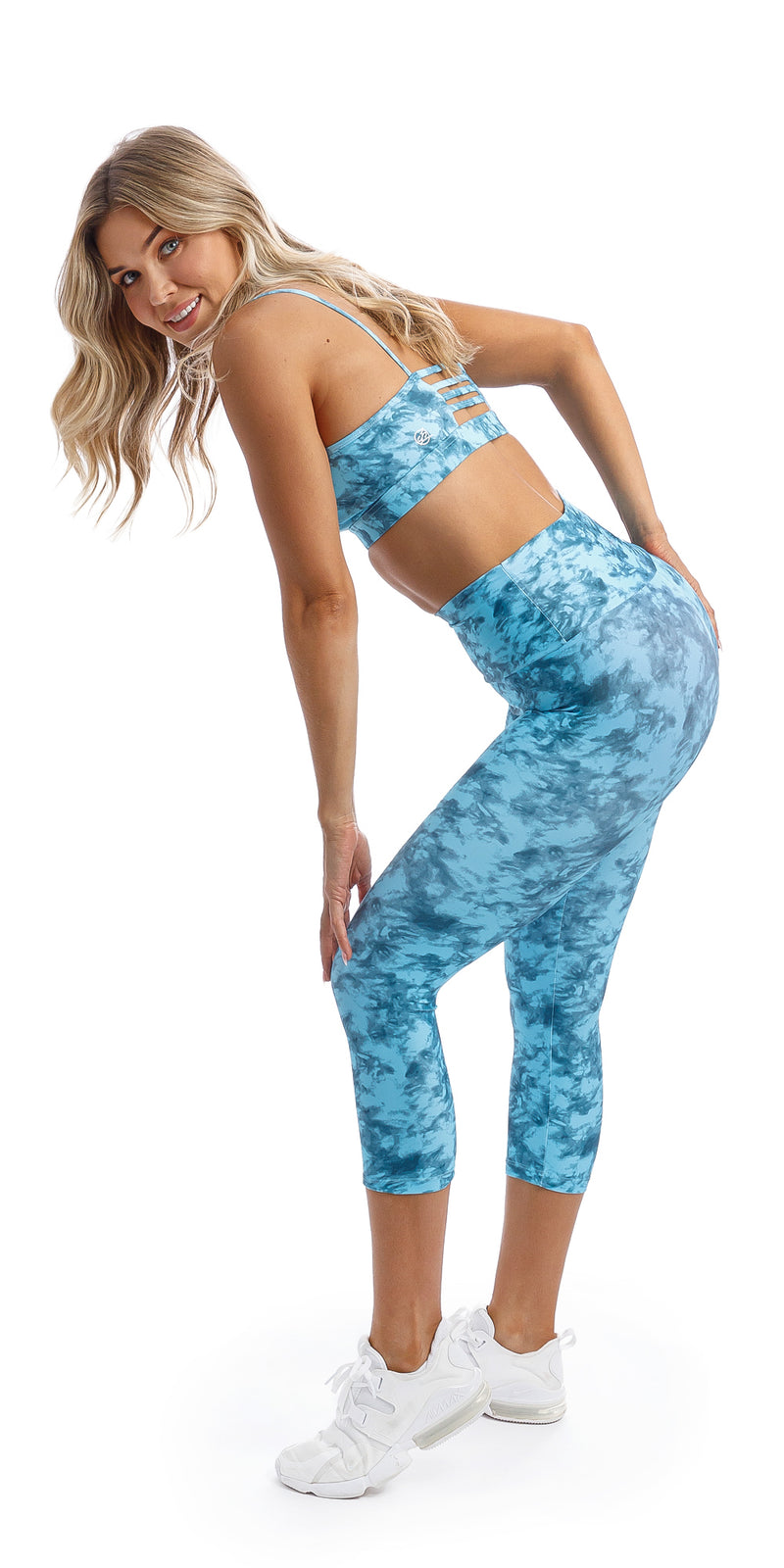 Girl bending over wearing blue tie dye blue crush print ultra high waist capri leggings & matching racer back bra
