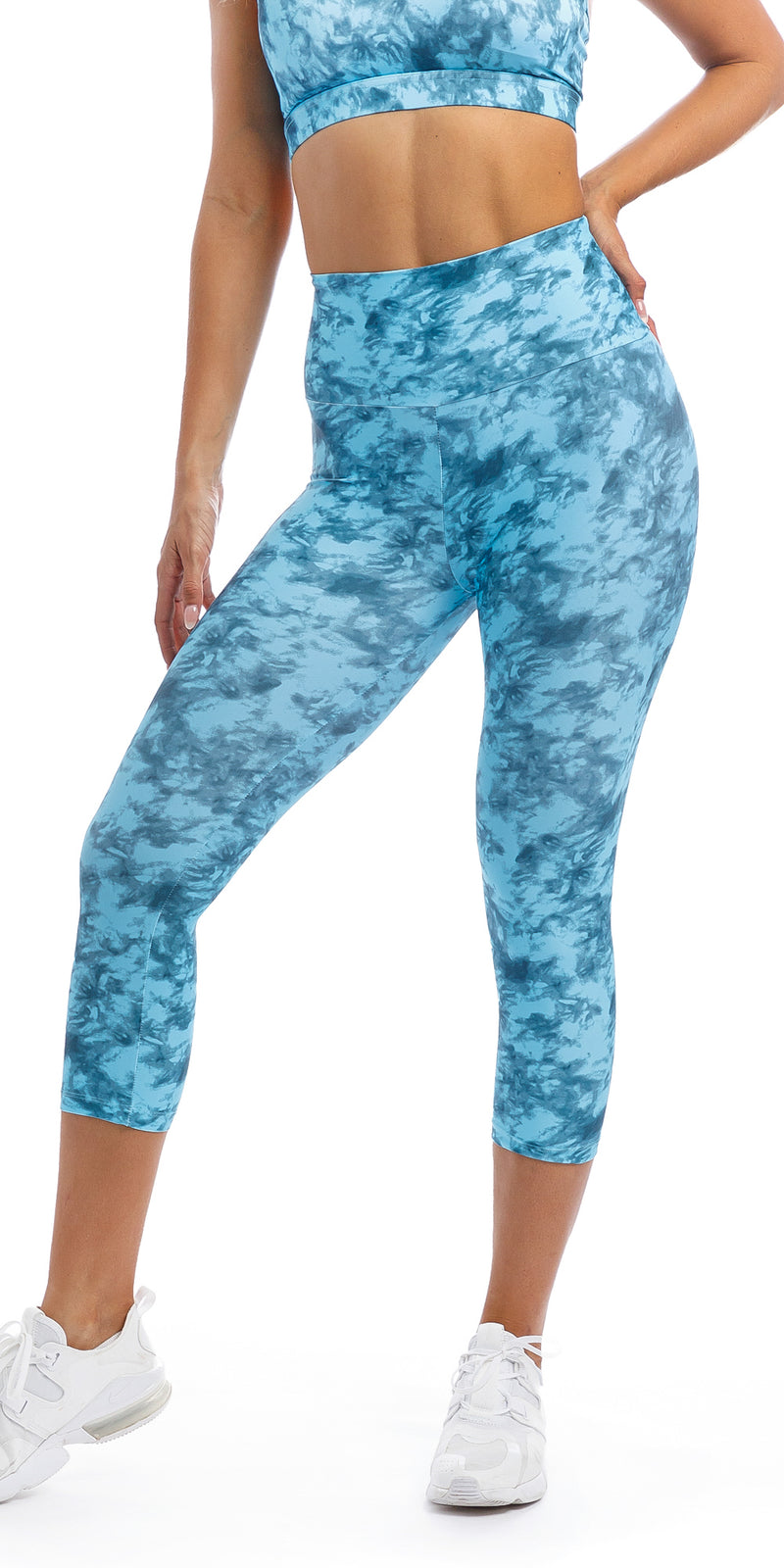 Girl with hand on hip wearing blue tie dye blue crush print ultra high waist capri leggings & matching racer back bra