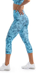Side View: Girl with hands on hips wearing blue tie dye blue crush print ultra high waist capri leggings & matching racer back bra