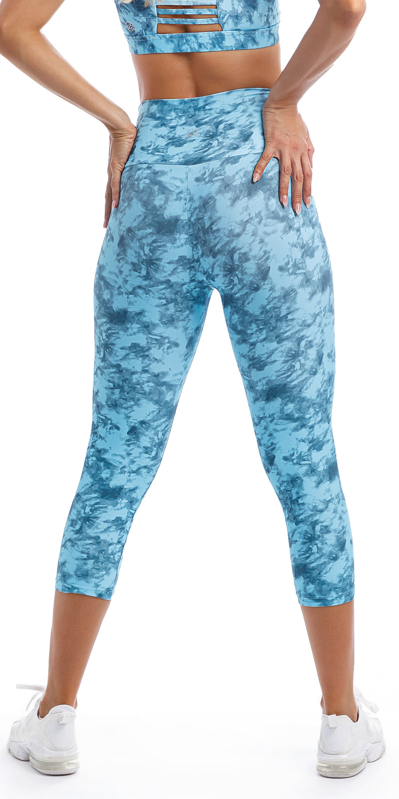 Rear View: Girl with hands on hips wearing blue tie dye blue crush print ultra high waist capri leggings & matching racer back bra