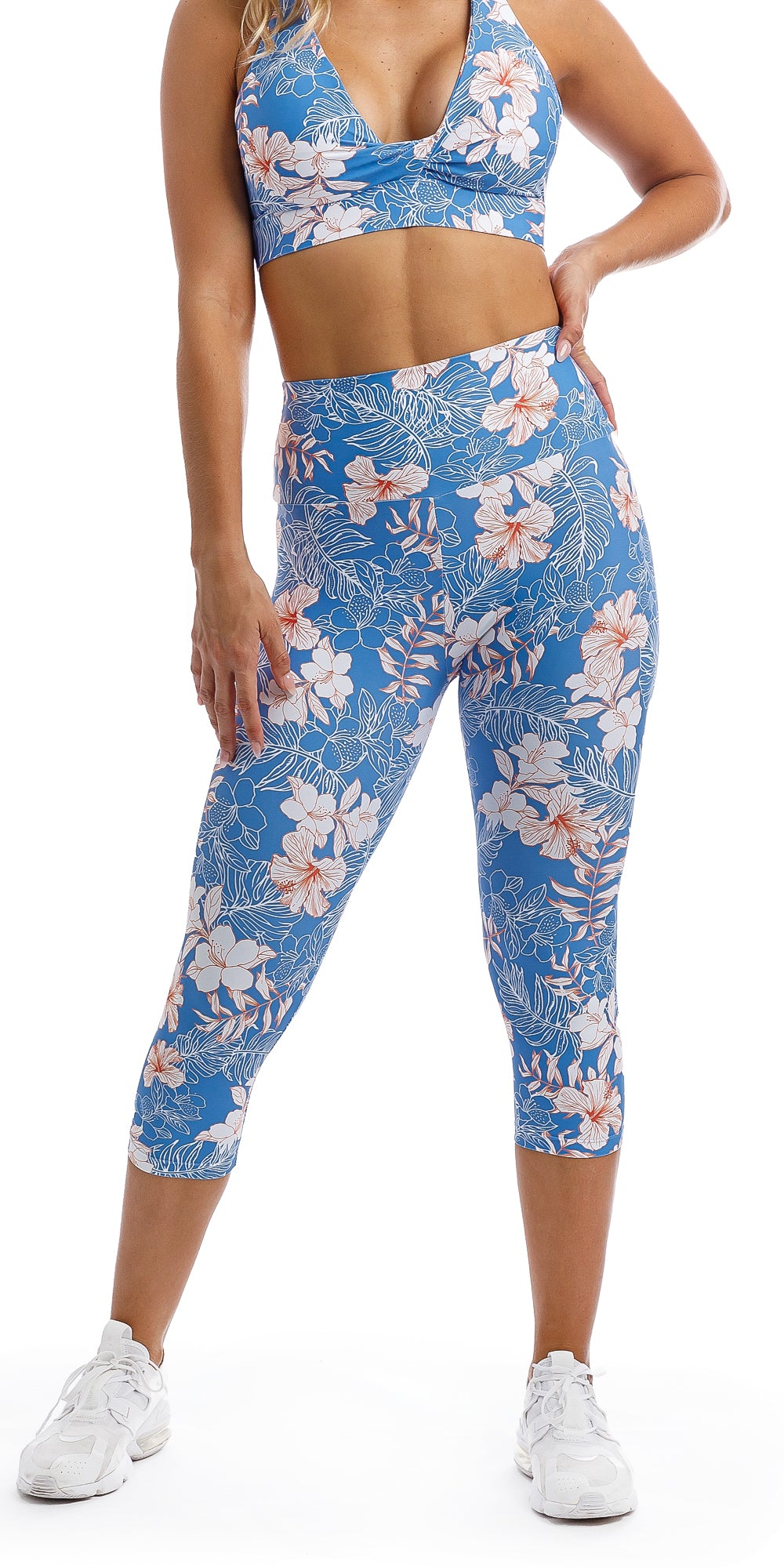 Lady wearing blue, white, pink floral Hibiscus Kiss print capri leggings & matching infinity bra
