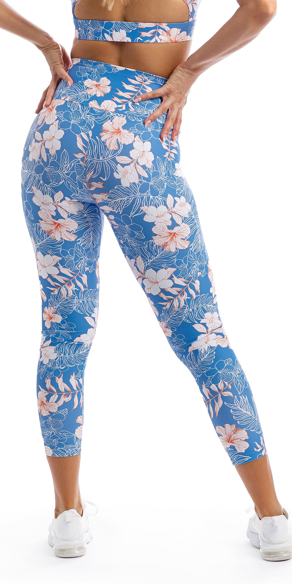 Lady wearing blue, white, pink floral Hibiscus Kiss print ultra high waist 7/8 leggings & matching infinity bra