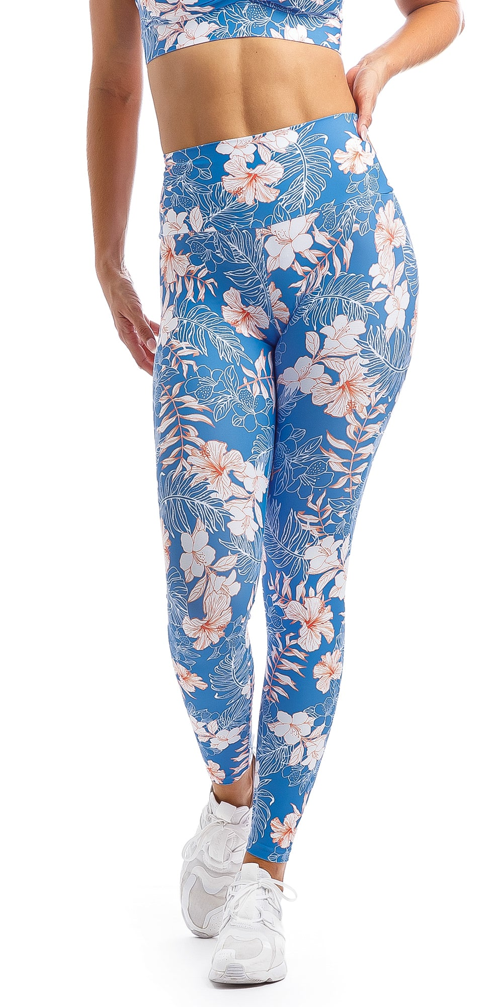 Lady with hand on hip wearing blue, white, pink floral Hibiscus Kiss print ultra high waist leggings & matching infinity bra