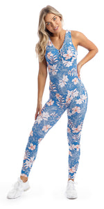 Lady with hand on hip in sleeveless blue, white and pink hibiscus flower print unitard with crisscross back detailing