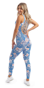 Rear view of lady with hand on hip in sleeveless blue, white and pink hibiscus flower print unitard with crisscross back detailing