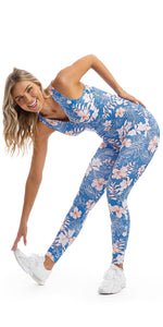 Lady stretching touching toes in sleeveless blue, white and pink hibiscus flower print unitard with crisscross back detailing