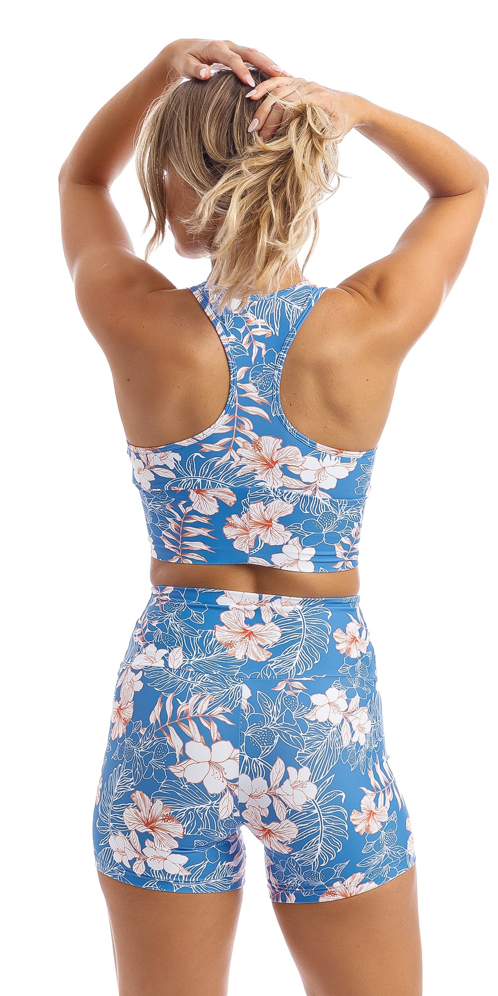 Rear view of lady wearing blue, white, pink floral Hibiscus Kiss print racer back bra & matching midi shorts