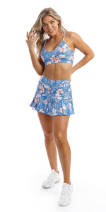 Lady wearing blue, white, pink floral Hibiscus Kiss print skort & matching momentum bra