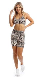 Girl flicking hair wearing brown & white cheetah print midi shorts with pockets & matching momentum bra