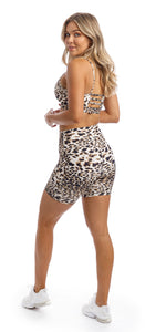 Rear view of girl wearing brown & white cheetah print midi shorts with pockets & matching momentum bra